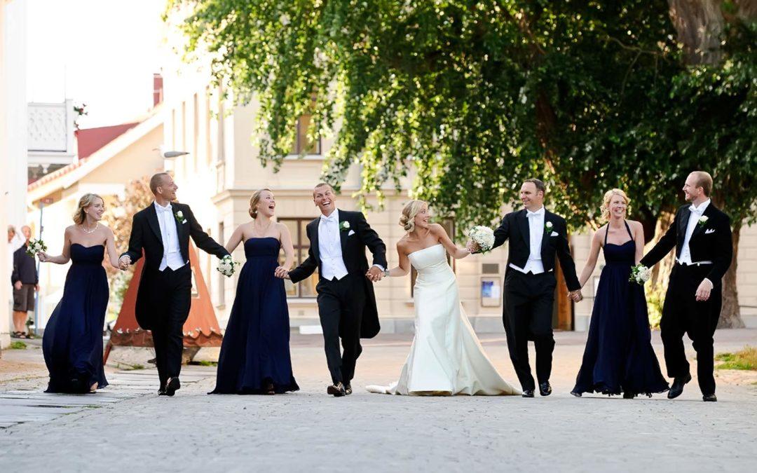Maria och Martin från Stockholm hade sitt bröllop på Marstrand och här har Stig Albansson fotograferat dem med deras brudfölje i riktning mot kyrkan med Silverpoppeln skymtandes i bakgrunden. Trädet som är Kungälv kommuns största träd.