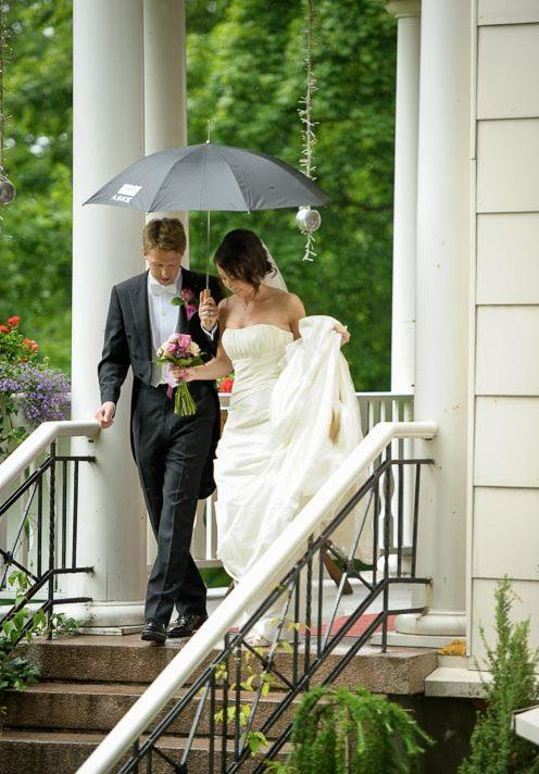 Brudpar går ner för trappan i lätt regn. Villa Odinslund Göteborg.